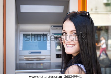 woman looking back and inserting credit card to ATM - stock photo