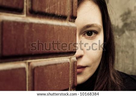 Woman looking behind a brick wall. - stock photo