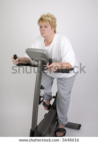 woman looking bored on exercise bike - stock photo