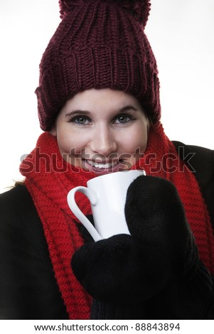 woman looking cold in winter clothes drinking a hot drink to keep warm