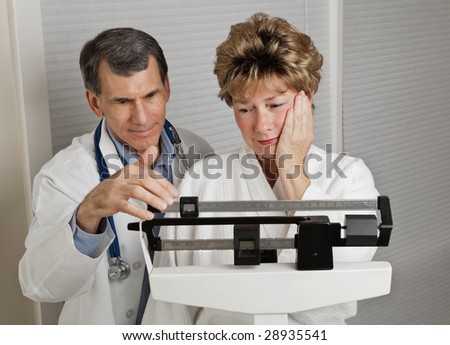 Woman looking dismayed at her weight as she is weighed by her doctor on a medical scale. - stock photo