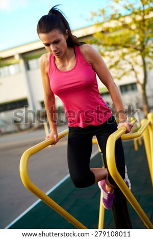 Woman looking down doing tricep dips on a dip stand outside with ankles crossed. - stock photo