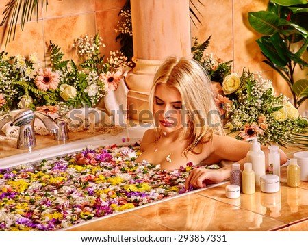 Woman looking down relaxing at water spa with flower petal. - stock photo