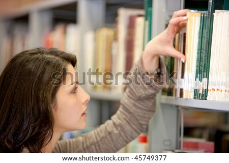 Woman looking for a book at the library - stock photo