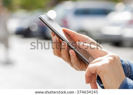 Woman looking for her car with mobile phone in parking car - stock photo