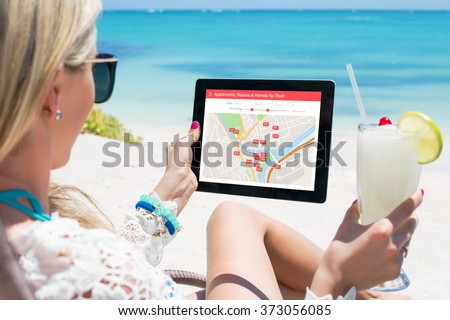 Woman looking for places to stay on room booking app - stock photo