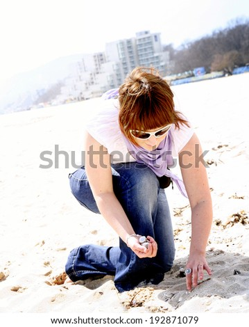 Woman looking for scallop on the beach.