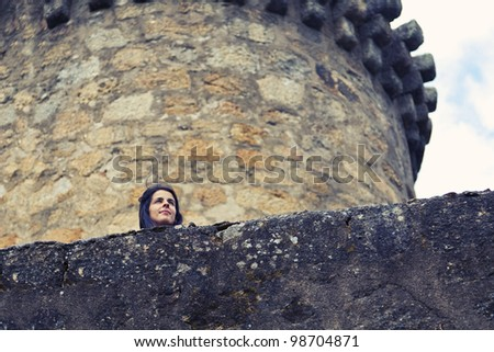 Woman looking from a castle turret - stock photo