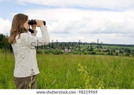 Woman looking in binoculars. - stock photo