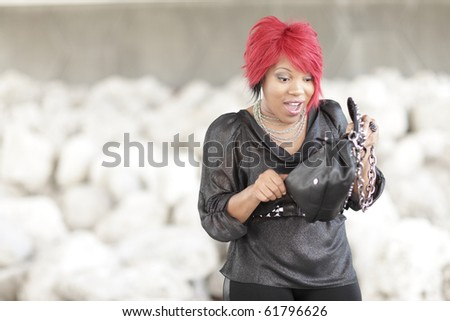 Woman looking in her handbag - stock photo