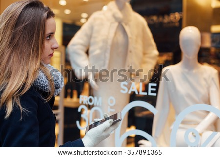 Woman looking in the boutique showcase and holding mobile phone - stock photo