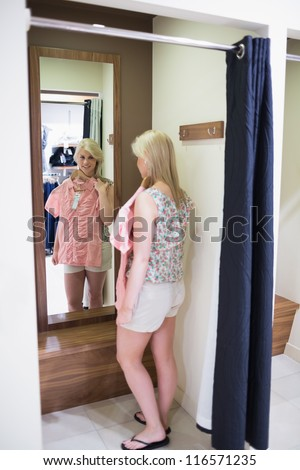Woman looking in the mirror standing in the changing room - stock photo