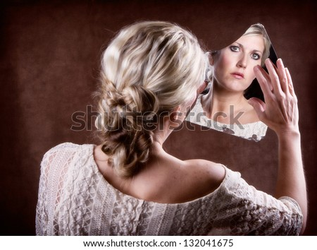 Woman looking into a broken mirror touching it with her hand, with back of head showing - stock photo