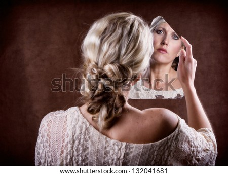 Woman looking into a broken mirror with a sad look,  back of head showing - stock photo