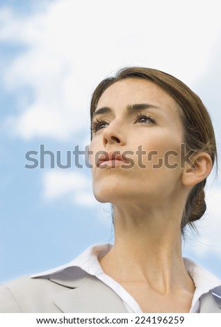 Woman looking into distance, portrait, low angle view - stock photo
