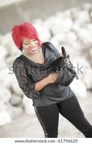 Woman looking into her handbag and smiling - stock photo