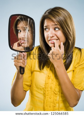 Woman looking into shattered mirror nervously