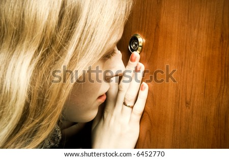 Woman looking into spy hole. - stock photo