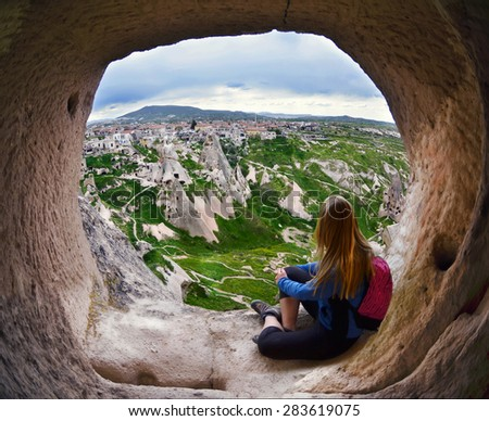 Woman looking into the distance against the background of incredible landscape with  mountains , geological structures in Goreme, Cappadocia,  Turkey - stock photo