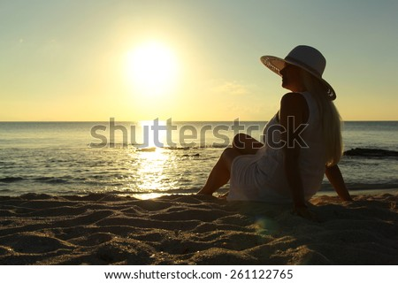 Woman looking into the sunset on the beach - stock photo
