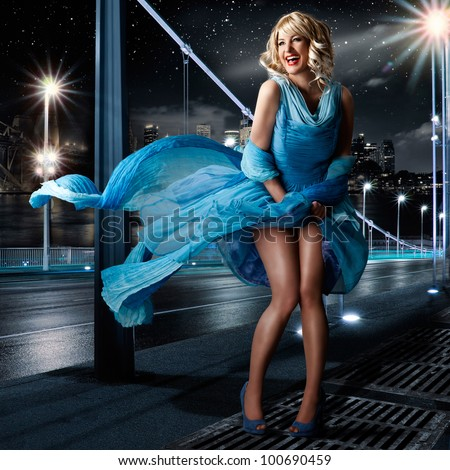 woman looking like Marilyn Monroe standing with a dress in the wind - stock photo