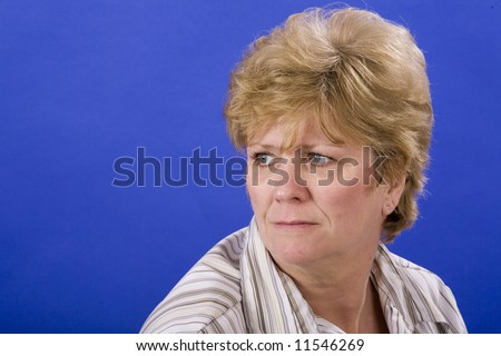 woman looking melancholy on blue back ground - stock photo