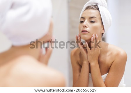 Woman looking on reflection in the mirror after shower  - stock photo
