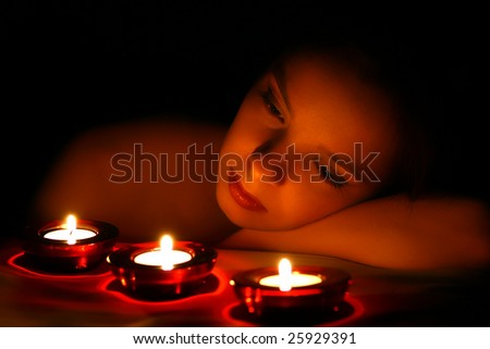 Woman looking on three candles - stock photo