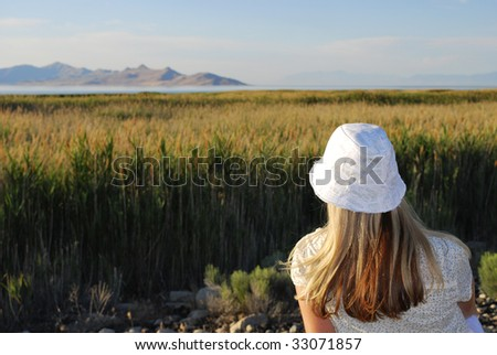 Woman looking over a tall field of grass - stock photo
