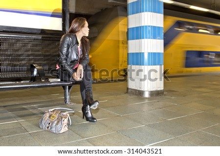 Woman looking over her shoulder at a passing train in an underground railway station, sitting on a bench, with a book beside her and a purse on the platform floor - stock photo