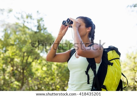 Woman looking something with binoculars on the wood - stock photo
