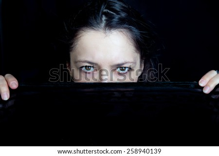 Woman looking sternly from behind a black veil she holds - stock photo