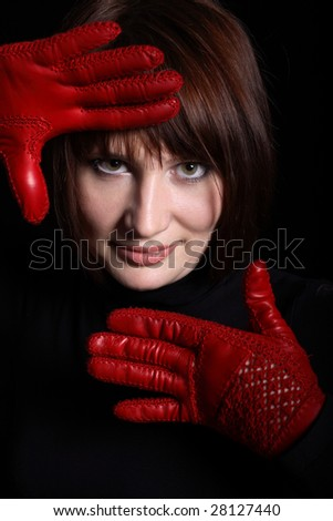 Woman looking straight from dark. In front of her red gloves on her hands. Vertical - stock photo