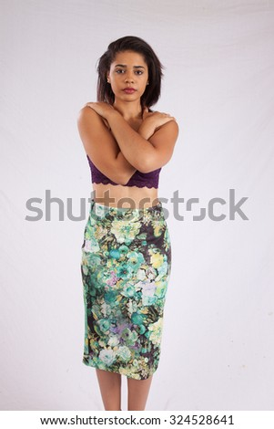 Woman looking thoughtfully at the camera with her arms crossed across her chest - stock photo