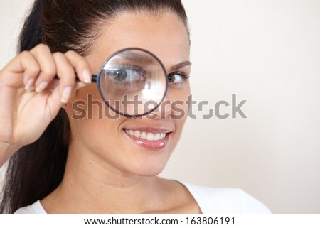 woman looking through a magnifying glass - stock photo