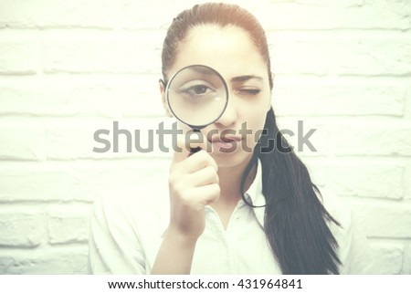 woman  looking through a magnifying glass brick wall background - stock photo