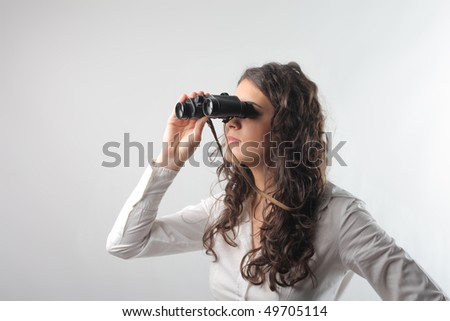 Woman looking through a pair of binoculars - stock photo