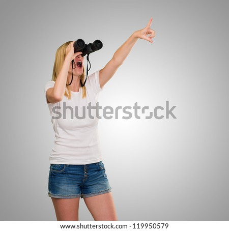 Woman Looking Through Binoculars against a grey background - stock photo