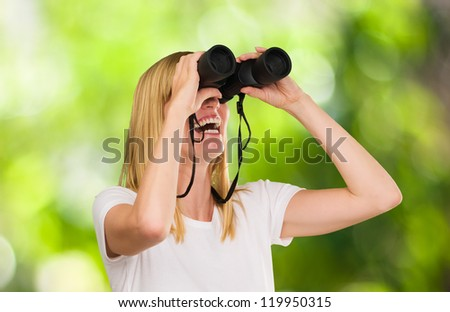 Woman Looking Through Binoculars against a nature background - stock photo