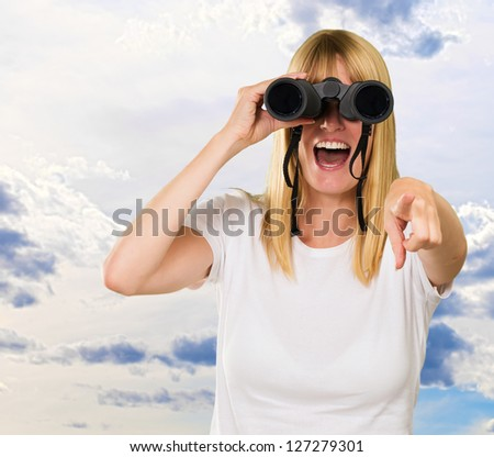 woman looking through binoculars and pointing against a cloudy sky background - stock photo