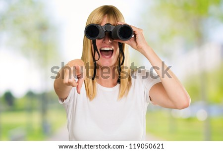 woman looking through binoculars and pointing at the park - stock photo