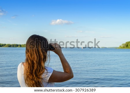 Woman looking through binoculars as a for a bright future, landscape out of focus, focus foreground - stock photo