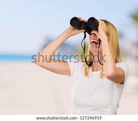 Woman Looking Through Binoculars at a beach - stock photo