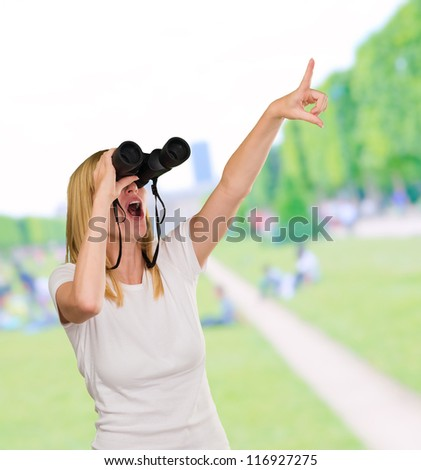 Woman Looking Through Binoculars at the park - stock photo