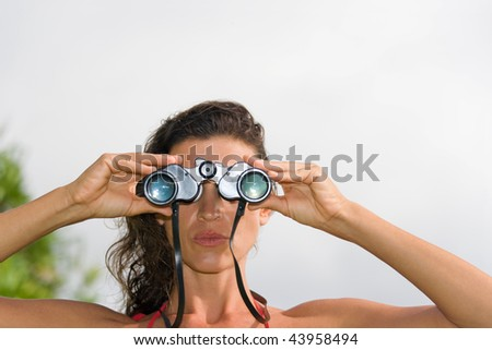 woman looking through binoculars in nature with white background