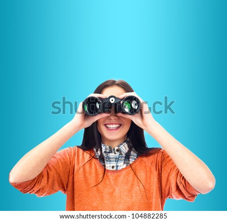 Woman looking through binoculars isolated on blue - stock photo