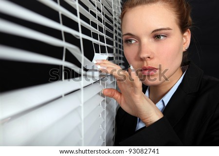 Woman looking through blinds - stock photo