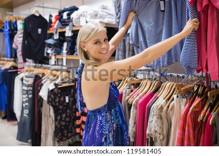 Woman  looking through clothes and smiling in shopping mall - stock photo