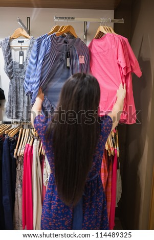 Woman looking through clothes rail in shopping mall - stock photo