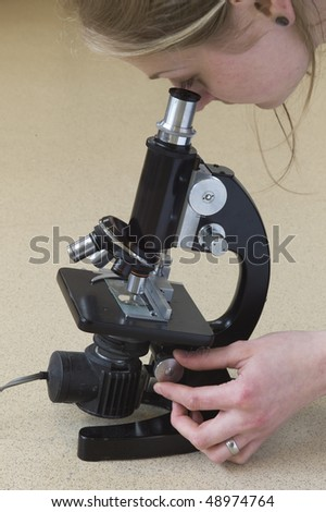 Woman looking through microscope - stock photo